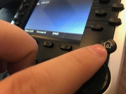 Polycom VVX IP phone, with a finger pointing towards the Home Button.