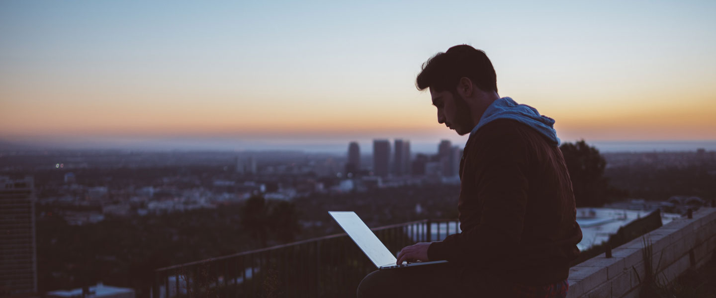 A man sitting upon a peak, overlooking a city, working on his laptop computer at dawn.