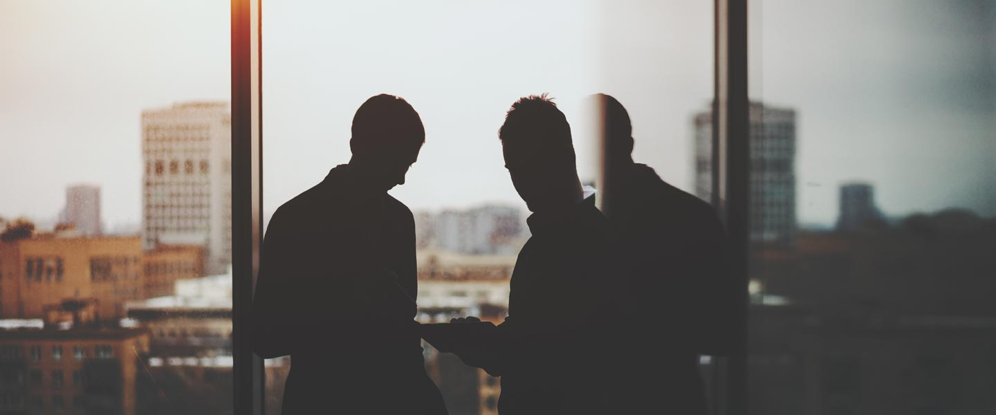 Two men stand in serious conversation while looking outside of their skyrise office space.